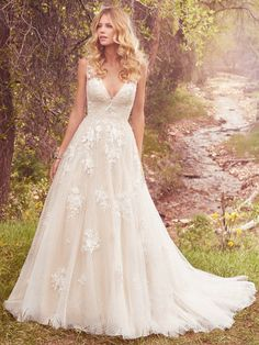 Maggie Sottero - MERYL, This vintage-inspired ballgown features lace appliqués over whimsical layers of dotted tulle and Chic organza. Featuring a V-neckline, illusion straps accented with lace appliqués, and square back. Swarovski crystals and beading add shimmer and ethereal texture. Finished with covered buttons over zipper closure.