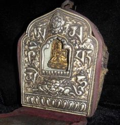 Tibetan Guru prayer box metal & White tara Buddha with DragonsA Ghau is traditionally used by Buddhist during their travels as a prayer box.   It usually holds a sacred deity inside.  This one is made of handcarved Tibetan silver. Tsatsa clay and cloth pieces inside ...