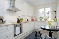 The plaid in this kitchen is surprisingly fresh with the light color palate. I also love the small kitchen table with ghost chairs. Great way to utilize a small space!
