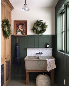 dark green board and batten with wood accents and an industrial sink