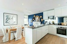 Diy kitchen wall decor kitchen with blue wall chairs dining area flat panel gray countertop oven recessed lights slipcovers table wall art white cabinets Kitchen Wall Art, Diy Kitchen, Kitchen Decor, Kitchen Office, Kitchen Dining, Blue Accent Walls, Blue Walls, White Kitchen Interior, Cocina Diy