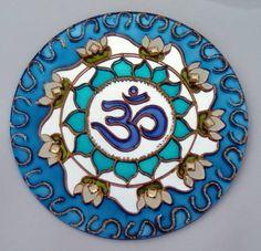 Espelho de 15cm de diâmetro, pintura vitral, decorado com pedrinhas em acrílico e tinta relevo dourada. Om (?) é o mantra mais importante do hinduísmo e outras religiões. Diz-se que ele contém o conhecimento dos Vedas e é considerado o corpo sonoro do Absoluto. O Om é o som do universo e a sem...