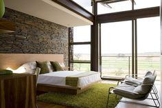 schlafzimmer wandgestaltung natursteinwand holzbett shaggy teppich grün