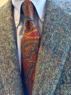 Magee Donegal Wool cloth with random flecks of colorful wool thread tossed onto the loom. I'm very fond of Donegal tweed, and own two 3/2 roll, 100% wool, sport coats in this flecked style, two 60% wool, 35% mohair, 5% cashmere sport coats in Gamekeeper tweed patterns, and three hand loomed 60% wool, 35% mohair, and 5% cashmere sport coats in a broken bone pattern. I am trying to  break my addiction to Magee Donegal sport coats!. Sam Hober Silk Paisley.