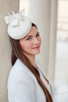 Minimalistic design of this wool pillbox makes it very versatile accessory for contemporary bride or any formal event.  The bridal pillbox is made of millinery buckram covered with quality velour wool in ivory colour. It is adorned with bows trimming and pearl center.  The bridal hat attaches to the hair with hat elastic, easily covered by hair when placing it. Interior lining is in matching colour.