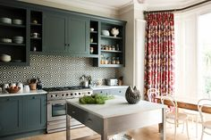 Love the combination of colors created with this kitchen's eclectic tile, bold drapery, and deep-green cabinetry. The playful ikat print on the luxurious drapes softens the bold geometric backsplash, making the space feel cozy rather than jarring.