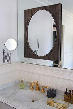 Layer a mirror over standard builder mirror in bathroom