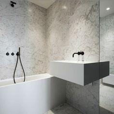 White bathroom with black fittings. Good idea to have movable hose/tap over bath for kids and puppies!