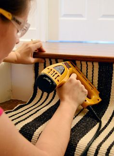 Sherry using electric staple gun to apply stapes to black and white runner under first tread White Runners, Staircase Runner, Staircase Makeover, Staircase Remodel, Young House Love, Basement Stairs, Basement Bathroom, Carpet Stairs, Diy