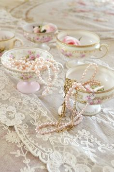 Pale pink pearls in floral tea cups on a table of antique lace.