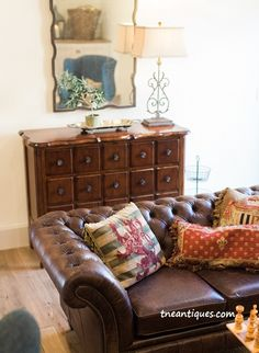 A cozy  game room features a tufted leather sofa from England and Aubusson pillows.