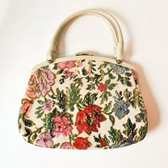 Beautiful, High Quality Vintage 1960s Carpet Tapestry Bag. Dual Handles. Creamy Vinyl Trimmings & Handles. Secured Lift Lock Closure. Vivid, Brightly Colored Floral of Pink, Green, Red, Brown, and more. Cream Grosgrain Interior, with Metal Zipper Compact Pocket. From the Famous Garey Purse Company, this Purse is Very Well Made, and in Clean, Top Notch Vintage Condition.