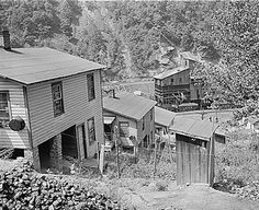 View from Southern Coal Corporation's coal camp at Bradshaw. I think this photo says it all about Appalachian coal town life in the 1940's. You have the wash tubs hanging on the house; the outhouses; pile of house coal (lower left); and the tipple at the bottom of the hill.- MCDOWELL COUNTY