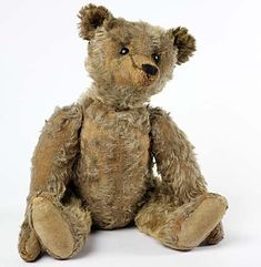 A photo of a small old light brown teddy bear sitting upright on a white surface