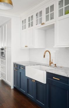 Two-toned kitchen features white upper cabinets and blue lower cabinets agreeing with brass hardware and white horizontal backsplash tiles. Kitchen Room Design, Kitchen Cabinet Design, Kitchen Redo, Home Decor Kitchen, Interior Design Kitchen, Home Kitchens, Blue Kitchen Ideas, Blue Kitchen Inspiration, Blue Kitchen Designs
