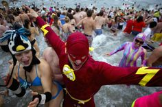 Participants run into English Bay during the 94th annual New Year's Day Polar Bear Swim in Vancouver