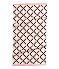 Een rechthoekig vloerkleed van geweven katoen met een geprint dessin op de bovenkant.