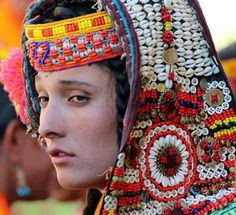 Kalash Pictures: A Kalash girl with colourful headdress made of cowrie shells - Kalash Valleys Photos, Chitral, Pakistan