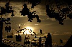 El sol se oculta tras las nubes mientras unas personas disfrutan de los juegos mecánicos en una feria en Nueva Jersey.  Foto: AP