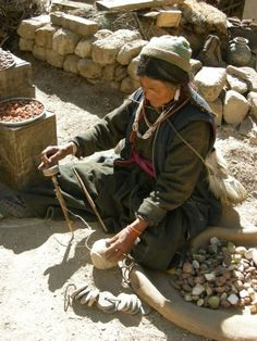 Plying yarn ladakh, India.  Whorls are stored separately, strung together as in the foreground.