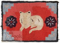"American hooked rug, 20th c., of a reclining cat, flanked by floral rosettes, 29"" x 41""."