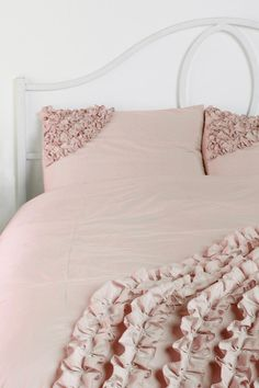 Pretty ruffled bedding with a light pink tint.