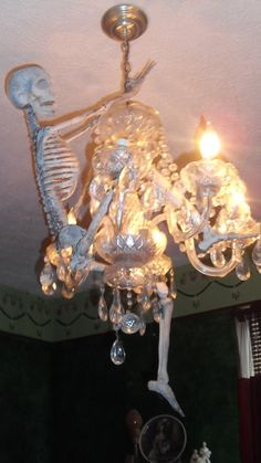 Halloween Party Decoration.  Skeleton hanging on to chandelier.  Diy holiday decorating ideas.