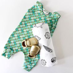 """""""I would rather be a mermaid""""  except then I wouldn't get to wear these moccasins! @modernburlap is currently having a 20% off today! Go check them out, unfortunately they are out of this seashell swaddle!  #shopsmall #annikensbabyattic #organic #organicbaby #organickids #organiccotton #organicromper #swag #sweetnswag #modernburlap #mermaid #mermaidromper #mermaidscales #goldmoccasins #bling #swaddleblanket #swaddle"""