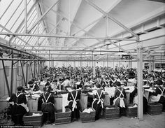 Women in dark dresses and aprons are pictured working in neat rows at the Cellular Clothing Company factory in Swindon in 1902