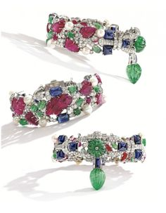 """Cartier """"Tutti-Frutti"""" bracelet  Estimated at $300,000-500,000, this bracelet incorporates pearls into the design. (Their inclusion is so unusual that Sotheby's thinks they may have been a specific client request.) The eight button-shaped pearls are woven among carved rubies and emeralds, smaller cabochon rubies, sugarloaf cabochon sapphires, and approximately 7.00 carats of diamonds in various cuts. A large carved emerald drop hangs from the clasp."""