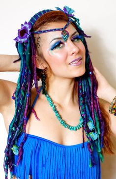 Turn heads with this vibrant sea goddess headdress! Many lush purple, blue, and turquoise hand dyed dreads/braids lay along side your natural hair.