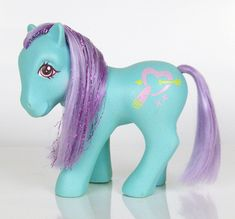 Kiss n' Make Up is an aqua-blue pony with pink eyes. Her hair is lavender, and she has purple metallic tinsel in her mane. Her symbol is a pink heart shot through with a yellow arrow, with a pink and yellow lipstick tube on one side and two small pink Xs. She is in the Crumpet Pose. Her lips turn bright pink when cold water is applied to them.       Kiss n' Make Up is a variation on the US Sweet Kisses Pony Ruby Lips, who is the same colors but was printed in a different pose and with a…