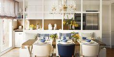 Comedor con mesa de madera, sillas azules y blancas, lámpara de araña, apoyado en una pared con cuarterones de cristal