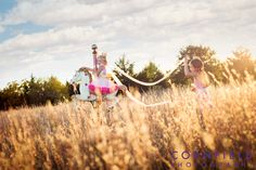 Whimsical sister portrait session in an open field with their carousel horse during sunset.  Cornfield Photography, 2015, Oklahoma City, OK.