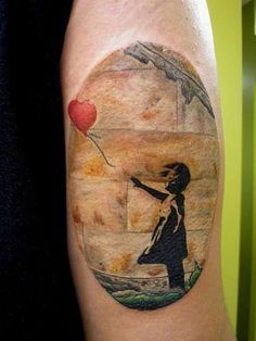 Beautiful Banksy tattoo. Love that the texture of the wall was still included.