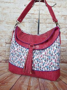 Hippo Hobo purse from the bag sewing pattern by Emkie Designs.  This example is a stunner in faux dragon vinyl and cotton feathers, by Charlotte S.