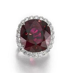 RUBELLITE AND DIAMOND RING.  Set with a cushion-shaped rubellite stated to weigh 22.21 carats, to a scalloped border and split shoulders set with brilliant-cut diamonds, size M ½.