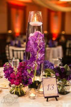 Tall glass bullet vases with black stones and purple vandalia orchids. Around these are smaller cylinders of purple stock, lisianthus, purple hydrangeas by Les Bouquets. Photograph by Artisan Photography. ~ Cosmopolitan Events