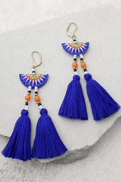 "Join the party in the Shashi Delaney Blue Tassel Earrings! A green, coral, white, and blue embroidered bead with gold, black, white, and coral beads tops trendy blue tassels. Earrings measure 5"" long."