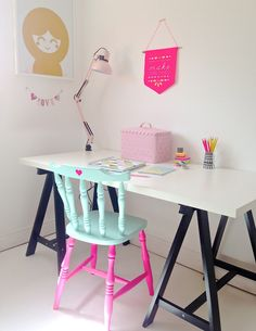 a white Ikea desktop with black trestle legs and up cycled chair painted mint green and neon pink makes a simple, uncluttered and modern workspace