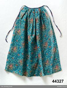 1830-1850. Västerfärnebo, Västmanland. Förkläde av tunt, kyprat ylletyg, yllemuslin. Tryckt blommönster i grönt, blått, vitt och lila samt röda och bruna nyanser.. Blomrankor i mellanblått mot blågrön bottenfärg. Veckad mot linning av halvsiden mönstrad i mörkblått och rödlila. Handsydd fåll nertill. Förkläde @ DigitaltMuseum.se