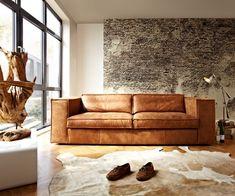 Cognac kleurige bank met stoer behangetje van bakstenen. Modern and industrial interior