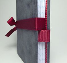 A different way to tie an album closed. Ribbon not attached to cover, simply secured behind signatures at spine.