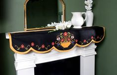 It is a black felt mantle or shelf runner with brightly colored folk art flowers and a mustard yellow trim. Description from ebay.com. I searched for this on bing.com/images