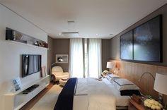 Esse painel de madeira ocupa toda a parede e é perfeito para destacar a cama box. Também adorei o móvel da tv, com nichos que abrigam os aparelhos e adornos. Projeto de Dado Castelo Branco. Foto: site do profissional.