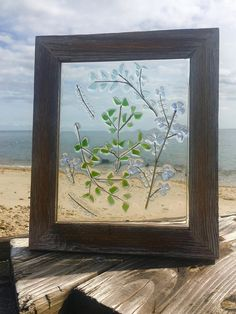 Beautiful barn wood framed floral sun catcher. Done with sea glass and natural glass in shades of blues and greens. These sun catchers are best hung in a window, on a light colored wall or back lit to get the full effect from the light shining thru the beach glass. The design is fused