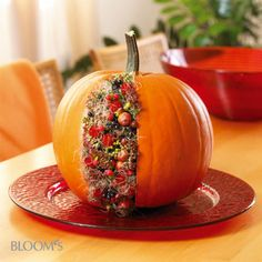 Pumpkin arrangement - A slice is cut from the fruit and filled with floral foam and autumn material