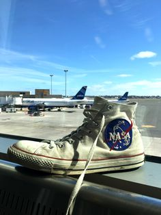 White Converse shoes with NASA patch sewn on