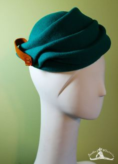 """The """"Diane""""  Gorgeous sculptural teal wool cloche with caramel wool tab and chunky amber colored vintage button. This is an amazing hat that will have people stopping you on the street with compliments! Vintage-inspired but with a modern flair.   $55"""