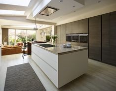 Snug Kitchens Newbury. Pronorm YLine kitchen with super matt crystal white base units, rift oak dark décor tall and mid units, Caesarstone shitake worktop and a solid oiled walnut breakfast bar.